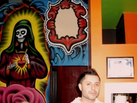Roman Torrez is backed by part of the Dia de los Muertos mural at Mr. Webo's, as well as the Blue Ribbon Award from Channel 4.