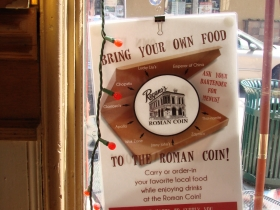 A sign in the window welcomes food from other venues.