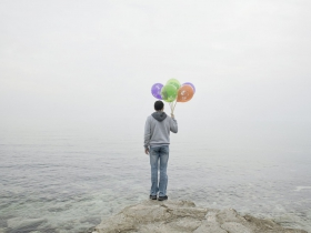Boy with balloons stays at the seashore in Aqtau, a town created in 1963 as a model socialist city for uranium miners. The mines are now closed; Aqtau is being remodeled as the City of Energy. Kazakhstan. 2013