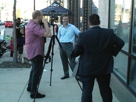 County Executive Chris Abele is interviewed outside Dream Bikes while aide Josh Zapfel (back to camera) looks on during Dream Street 2013.