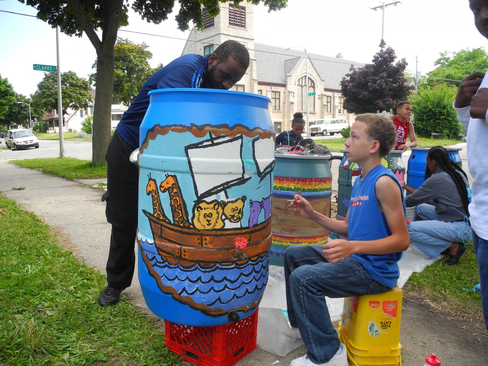 Kids painting water barrels at All Peoples Church