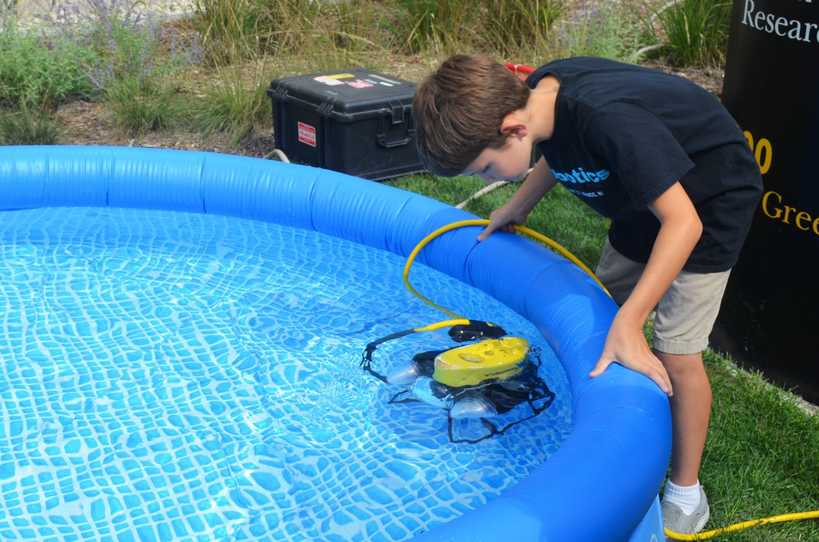 Child looks at an underwater robot from UWM School of Freshwater Sciences