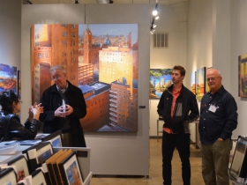 People surrounded by Hal Koenig's Urban Landscapes at Gallery Night and Day