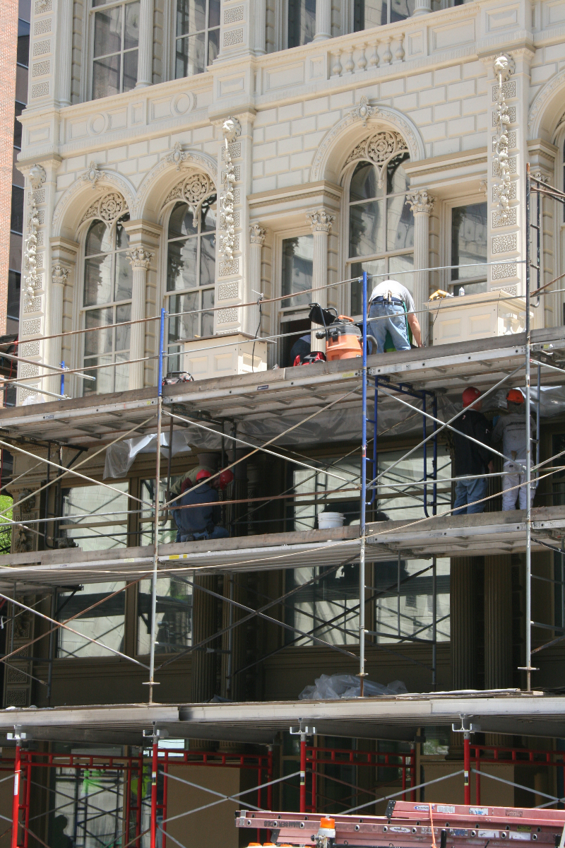 Construction workers putting finishing touches on the Iron Block Building.