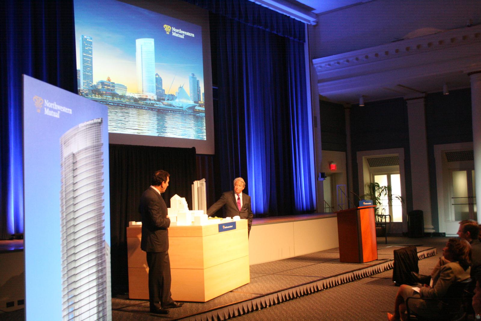 CEO John Schlifske and Jon Pickard look at the building model.
