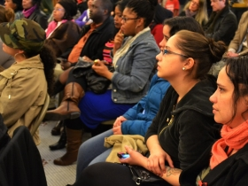 A full audience listens closely to political poetry.