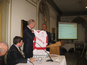 GMC Chair John Daniels (r) presents a Wisconsin Badgers Hockey jersey signed by coach Mike Eaves to Canadian, and hockey fan, Bill Downe, CEO of BMO Harris Financial at the monthly meeting of the GMC held at the University Club Monday, November 10th, 2014.