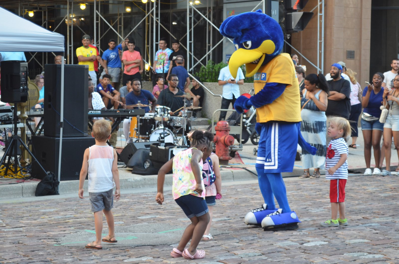 Children dance with the Secure Parking Mascot at the Night Market