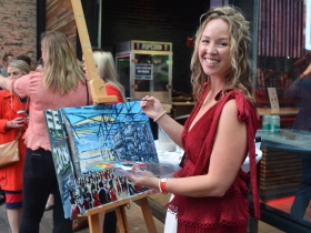 Katie Geis paints a picture live at Dinner in the Alley 2019