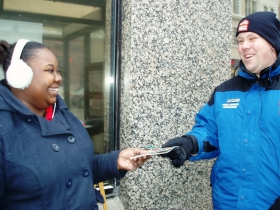 Andrea Brown is happy to receive an information packet from Justin Miller while she waits for a bus on W. Wisconsin Ave. Photo by Peggy Schulz