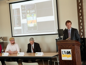 UWM Chancellor Michael Lovell (center) listens as Milwaukee County Executive Chris Abele reacts to the new mobile app created by UWM students for the county. Also pictured is Quinn Madsen (left of Lovell), who is the lead developer at the UWM Mobile Innovation Lab.