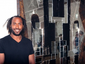 Portrait of Artist Rashid Johnson, next to his Falling Man, 2016 work made of burned red oak, black soap, wax, mirrored tile and spray enamel