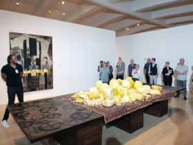 Rashid Johnson jokes with the press explaining his Falling Man series. In the foreground is a large worktable with an old Persian rug and rough blocks of shea butter