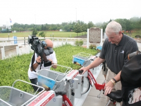 Mayor Barrett unlocks a b-cycle. Photo taken July 2013, by Dave Reid.