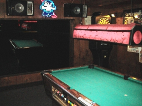 The back room pool table is reflected in a mirror. Watch your head on the wrought iron light above the table. Note also the table is open, and pool is free during Happy Hour. Photo by Michael Horne