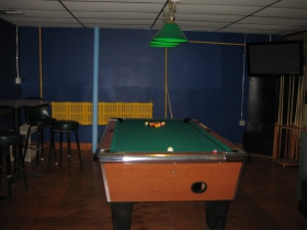 A Mondrian-esque palette awaits players in the pool room. Note the bright yellow radiator, and to its right, a very old fireplace, perhaps dating to the space's use as an 1880's bakery.