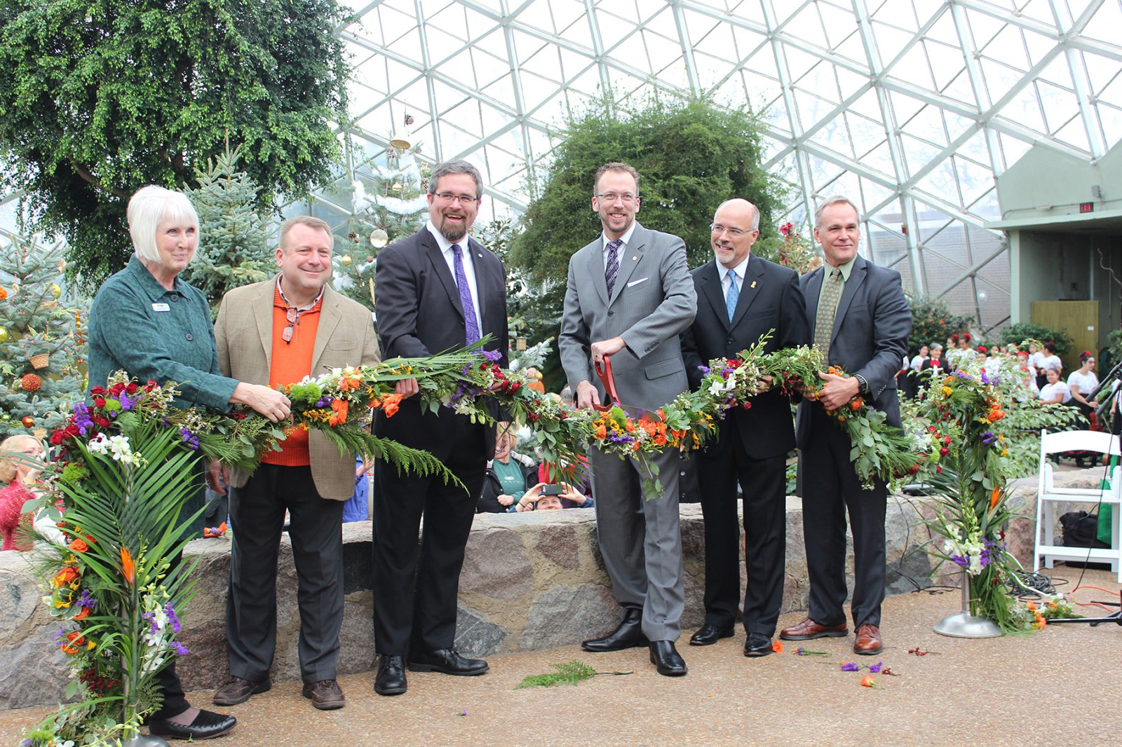 Officials cut a floral ribbon at the Domes Grand Reopening, December 1, 2016 L-R, Domes Director Sandy Folaron, State Rep. Josh Zepnick, Sup. Jason Haas, Sup. Theo Lipscomb, Northwestern Mutual President Eric Christopherson, Milwaukee County Parks Director John Dargle.