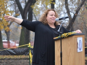 Michele Bria, the CEO of Journey House, points to the large pile of dirt that will soon be an NFL grade practice field