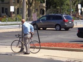 Ald. Kovac locking his bike up on a pole.