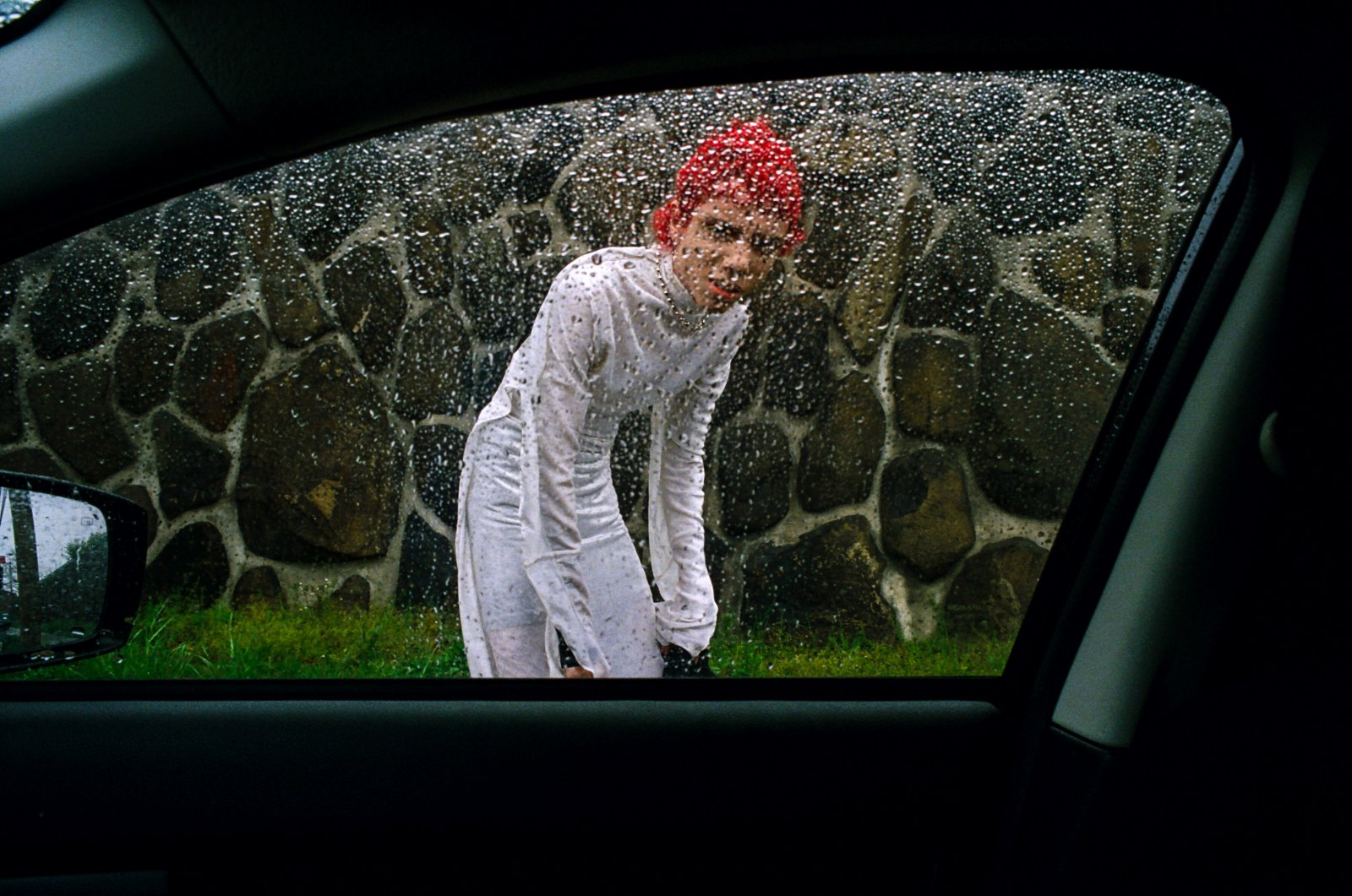A boy peers through a car window directly at the viewer