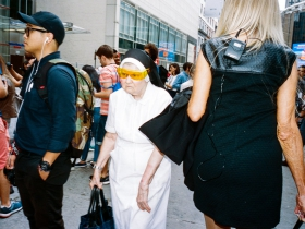 An ill-humored nun presses her way through a throng. She wears yellow fitover sunglasses perched precipitously over her coif and veil, but no glasses under her fitovers.