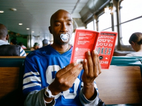 "A grown man reads at an indeterminate location with a pacifier in his mouth. The book is entitled ""Laugh-Out-Loud Jokes For Kids."" No kids are in sight. The man appears unamused."