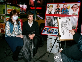A couple sits for a caricaturist. The woman wears a surgical mask, but not in the nearly finished drawing.