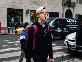 Again on a crosswalk, an otherwise unassuming teenager appears fierce through direct eye contact and a mouth made barbarous by balancing a tripod on his lower lip.