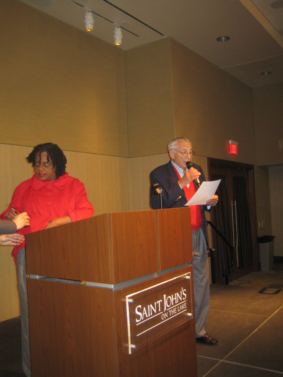 Gene Gilbert introduces Rep. Gwen Moore who is still fussing with her microphone at St. John\'s on the Lake Monday, December 30th, 2013.