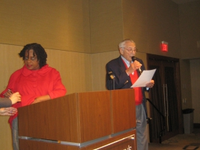 Gene Gilbert introduces Rep. Gwen Moore who is still fussing with her microphone at St. John's on the Lake Monday, December 30th, 2013. Photo by Michael Horne.