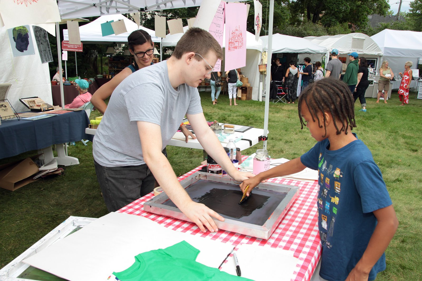 Ashia, from Wauwatosa, enjoyed the hands on print making demonstration by the UWM Print Narrative Forms Club at the Firefly Art Fair children\'s area