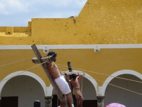 Jesus is raised up on the cross with one of the two criminals in the background