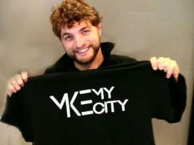 Ian Abston holding a MKE My City shirt.