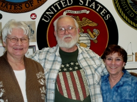 Nita and Tom Hundt and Jean Marie stand in front of some of the military emblems on the west well of the shop.  Photo by Peggy Schulz.