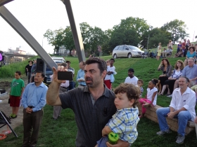Robert Joseph documents the event on his phone while holding his son, who sees grandma and grandpa on stage.