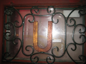 Sturdy ironwork on the front door includes the tavern's initial, readable from inside and out.