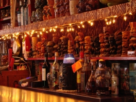 Small tiki statues decor behind the bar.