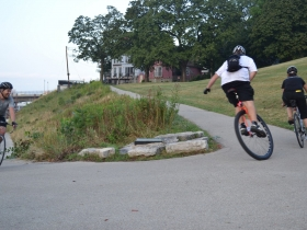 Unicyclist on the Verge of Passing a Rider Uphill