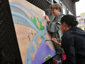 Ciera McKissick (foreground) and Ann Loper (background) paint a Silver City-inspired art piece.