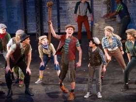 Jordan Arrasmith (Crutchie, center) with the cast of Skylight Music Theatre's production of Disney's Newsies running November 15 – December 29, 2019.