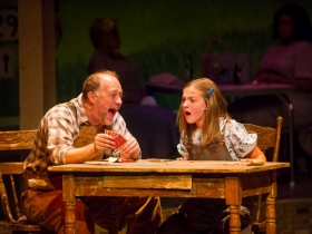 Foreground: Jeff Schaetzke (Father) and Kylee Hennes (Young Violet). Background: Cynthia Cobb (bus passenger) and Raven Dockery (bus passenger) in Skylight Music Theatre's Violet