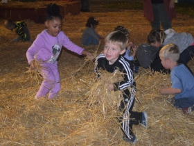 Children play in the straw at Harvest Fair 2019