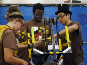 Students from FIRST Robotics Team 1675, Ultimate Protection Squad from Milwaukee, tinkering with their robot