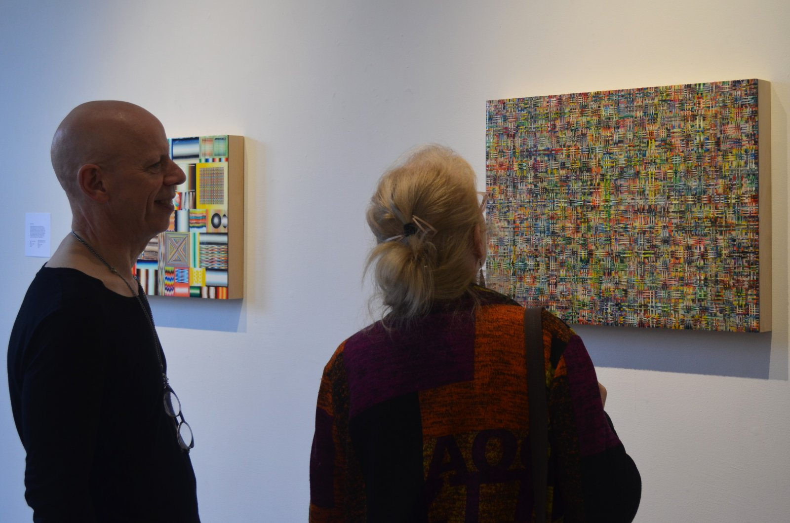 People look at works by Mark Ottens at Portrait Society Gallery