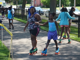 Children rollerskate on Columbia Playfields new walking path on the day of it reopening