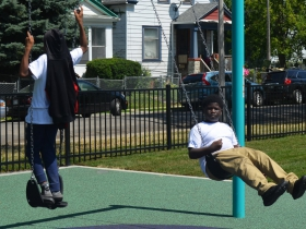 Children swing at Columbia Playfield on the day of its reopening