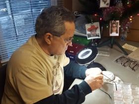 Chuck at his desk preparing eyeglasses for guests.