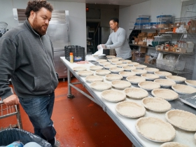 Jonathan Dye (left) looks on while his cousin Ronnie Herndon prepares pie crsuts to be filled.