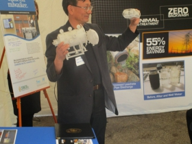 Douglas Hwang, president of CORNCOB, Inc., holds up a small replica of Alfie as he discusses the technology before a group of several dozen persons.