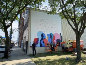 Desmond Mason paints a mural at 1335 N. Martin Luther King Jr. Drive.